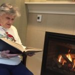 Reading by the fire warms Bea up!